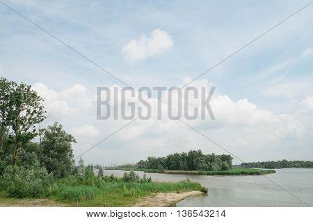 Lakeside landscape under a blue but cloudy sky