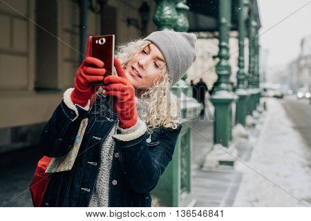Young blond curly female tourist in warm clothes and red gloves photographs or taking a selfie on city street, winter, snow