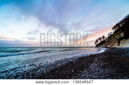 ultra wideangle sea landscape with stone beach and lilac purple evening atmosphere