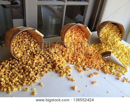 Open barrels of flavored popcorn on a white table.