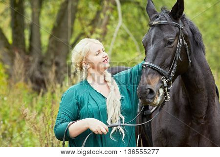 Blonde woman with plait in green clothes and chestnut horse in park.