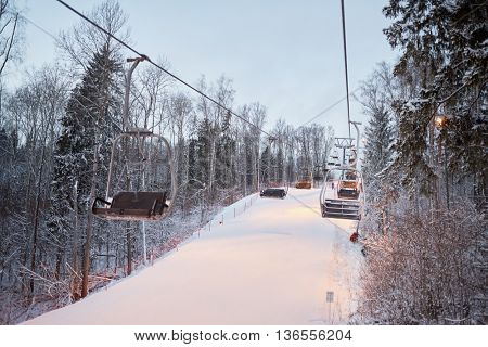 Cableway above track at ski resort in evening time.