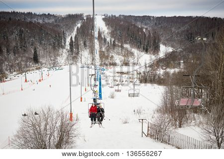 People rise on cableway on winter day at ski resort.