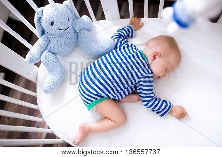 Sleeping baby and his toy in white crib. Nursery interior and bedding for kids. Cute little boy napping in bassinet. Kid taking a nap in white bedroom. Healthy child in bodysuit pajamas. poster