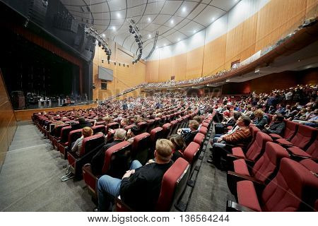 MOSCOW, RUSSIA - APR 24, 2015: People in armchairs in concert hall of Crocus city hall wait for band Secret show. Rock and roll band Secret founded in 1982 in Leningrad.