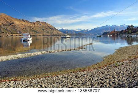 Lake Wanaka and boats with the Southern Alps in the background. Central Otago New Zealand. In the foreground note how low the lake level is after one of the hotest and driest drought Summers on record.