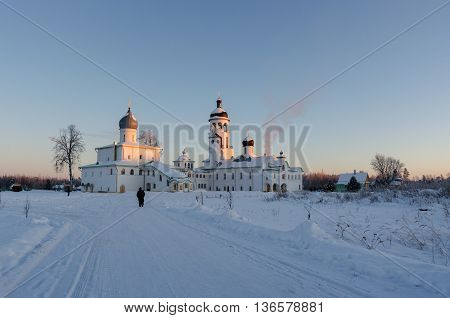 White russian ortodox monastery in winter day. Prist walking towards church