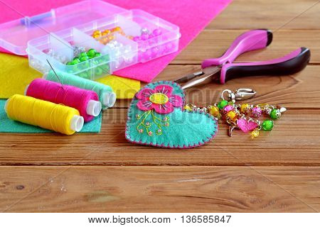 Beautiful keychain felt heart with colorful beads and flower. Box of beads, tools, sewing set, felt sheets on a wooden table. Children fabric project. Sewing and crafts idea for kids and adults