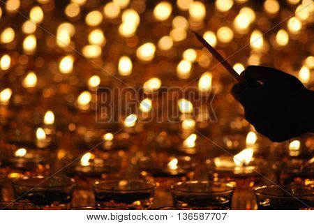 KUALA LUMPUR - MAY 16: A hand hold up candles during the celebration of Wesak day on May 16, 2011 in Kuala Lumpur, Malaysia. Wesak is informally called as Buddha's Birthday.