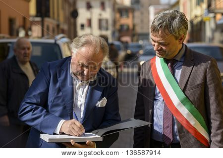 Sant'Agata Bolognese, Italy - April 30, 2016: Tonino Lamborghini donated to Mayor of Sant'Agata Bolognese , Giuseppe Vicinelli , a book of the history of Lamborghini cars signed by him during the parade for the 100th anniversary Ferruccio Lamborghini