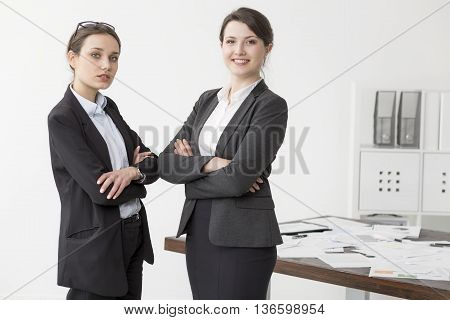 Two young busiesswomen posing on a light background