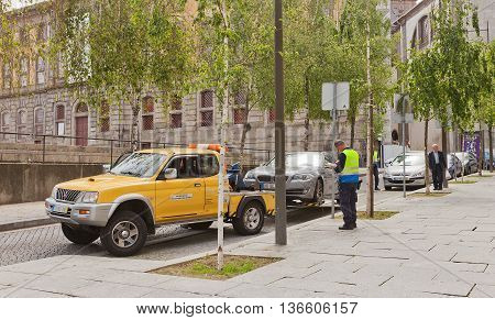 PORTO PORTUGAL - MAY 26 2016: Wrecker tows away improperly parked car in the center of Porto Portugal
