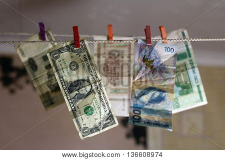 Money. Money laundering on clothesline. Colored clothespins.