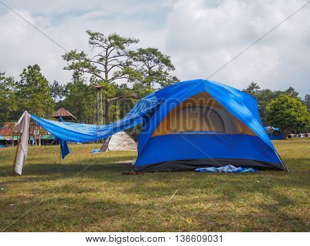 blue camping tent on the grass with cloudy sky