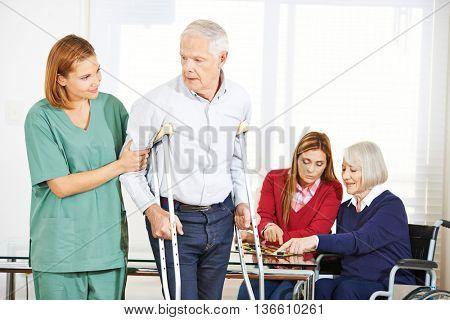 Geriatric caregiver with senior people in nursing home