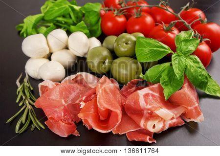 Prosciutto Smoked Pork Ham Rashers with cherry tomato mozzarella and olives on the wooden table