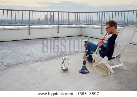 Man in glasses smoking hookah sitting on armchair on highrise roof at sunset.