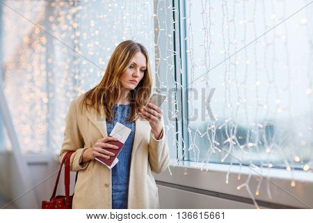 Tired woman at international airport with tickets and passport checking mobile for flight. Upset passenger waiting. Canceled flight due to pilot strike.