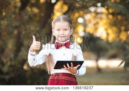 Smiling pupil girl 6-7 year old holding black tablet outdoors over nature background. Looking at camera. Thumb up.