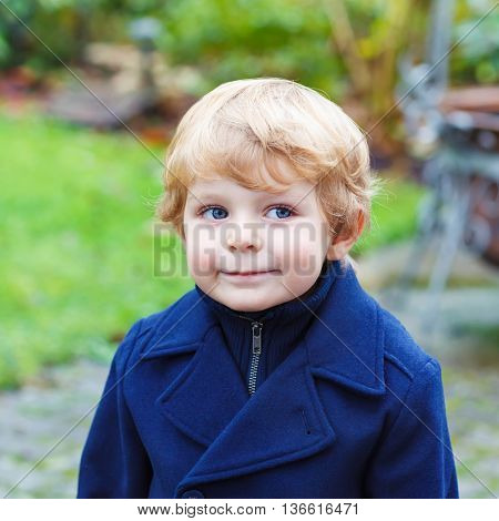 Happy little blond toddler boy walking on cold day in blue coat. Funny kid wearing wam clothes on cold autumn or spring day. Carefree childhood. Child having fun outdoors