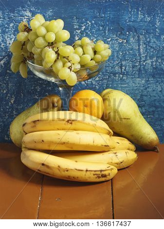 Still life with grapes bananas pears and tangerines on a blue background