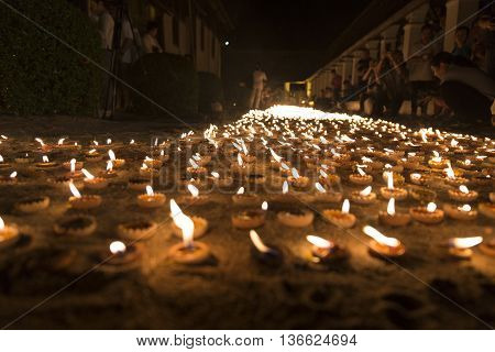CHIANG MAI, THAILAND - JUNE 10: People light candle to pay homage to buddha at Tonkwen temple in Chiang Mai, Thailand on June 10, 2016.
