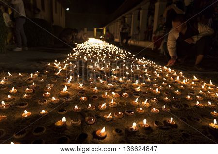 CHIANG MAI, THAILAND - JUNE 10: buddhist people light candle to pay homage to buddha at Tonkwen temple in Chiang Mai, Thailand on June 10, 2016.