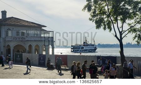 Istanbul Turkey - Mayer 29.2016: Kadikoy pier and the pier moving Kadikoy-Besiktas Ferry. Sea coast on the European continent seems to Hagia Sophia and the Blue Mosque silhouette.