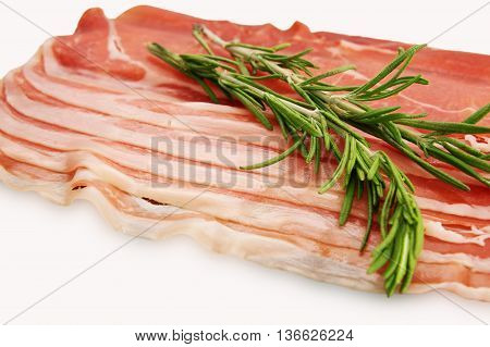 Prosciutto on a white background. Smoked pork rashers with rosemary