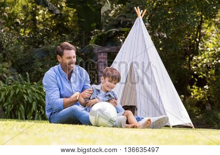 Cheerful father tickles his son at park. Happy child sitting outside a tent enjoying afternoon together with father. Father and son having fun with indian tent.