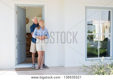 Happy mature couple embracing in front of the door. Smiling happy senior man and woman looking at each other on the doorstep of new house. Smiling husband embracing wife.