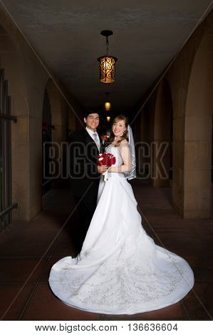 A formal portrait of a bride and groom on their wedding day.