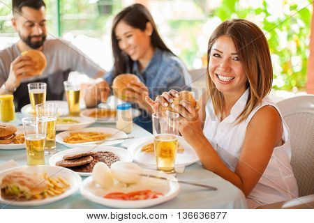 Portrait of a beautiful Latin girl eating a hamburger and drinking beer at a party with friends in a patio and smiling