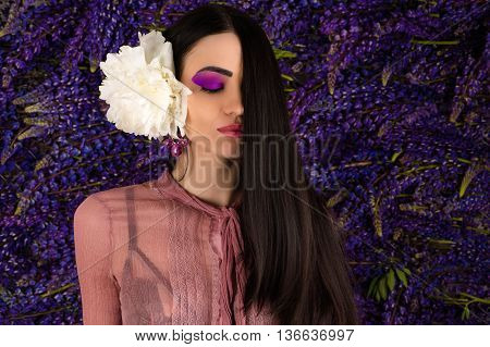 beautiful woman with peony in hair on background lupine flowers