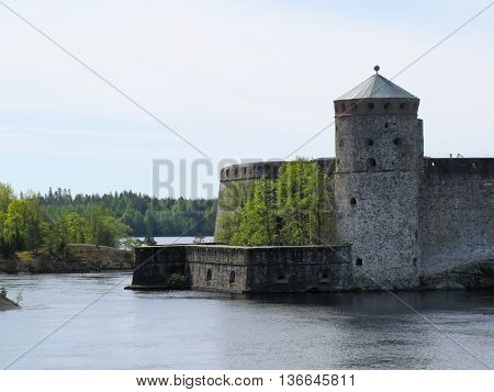 old castle by the river on a background of forest and blue sky