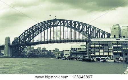Old style image of Sydney Harbor Bridge Australia with darkening rain clouds gathering above split tone image green hue