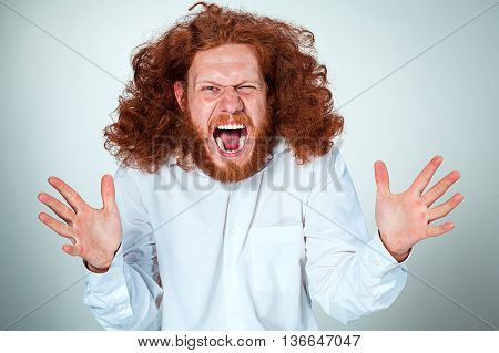 Portrait of screaming young man with long red hair and with shocked facial expression on gray background