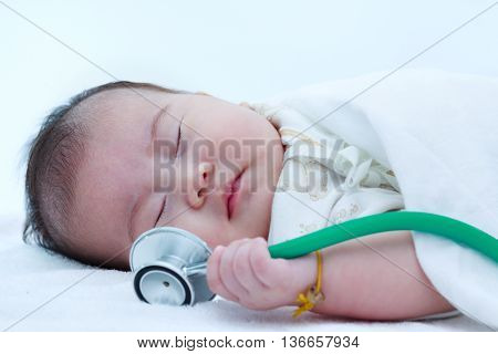 Healthy children concept. Closeup portrait of sleeping baby. Adorable asian girl sleeping peacefully with stethoscope on bed.
