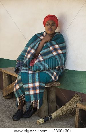 Gauteng, South Africa -  July 04, 2015:  Young beautiful Sesotho woman Bantu in traditional handmade colorful blue green blanket and orange hat next to her house  in Lesedi Cultural Village (unique center of African culture) .