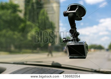 Action camera with suction cap on car windshield window filming the driving experience in urban traffic environment