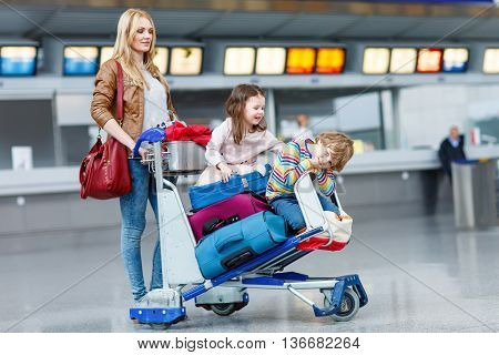 Happy family going on vacation. Mother and two little kids on international airport, sitting on suitcases. Brother and sister having fun and wating for flight
