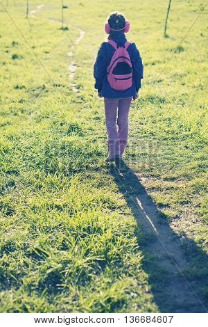 girl in ear muffs with backpack walking away by winding pathway