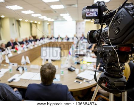 People sitting at a round table in the negotiations in the conference room. In the foreground TV video equipment for shooting