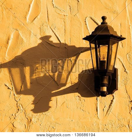 Wrought iron wall light on a whitewashed wall in the early morning sun Costa del Sol Malaga Province Andalucia Spain Western Europe.