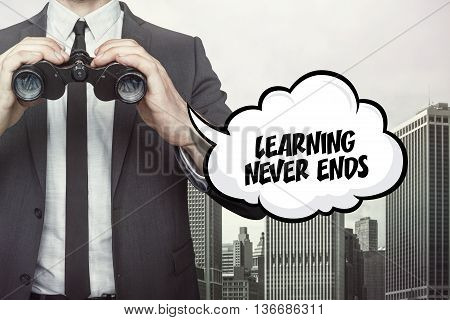 Learning never ends text on speech bubble with businessman holding binoculars on city background