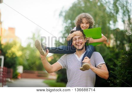 Little schoolboy sitting on the shoulders of his father and clings to his head. The father holds the boy's legs. The boy delighted. He likes to joke with dad. Father and son smiling happily. Back to school