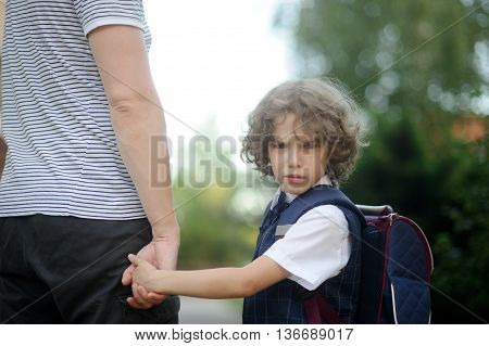 The father leads by the hand in school of the little schoolboy. The boy turned around and looked at the camera with an angry expression. The student does not want to go to school