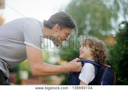 The father sends to school first-grader son. He carefully adjusts his backpack the boy and makes a funny face. The little schoolboy looks at dad with love. He smiles.