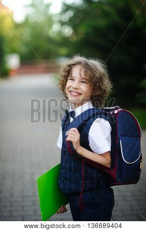 Cute little schoolboy standing on the sidewalk. It is elegantly dressed. Behind the boy a school backpack. The disciple holds a bright folder in a hand and smiles.