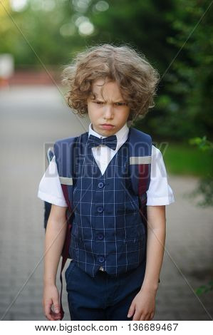 Little schoolboy stands in the school yard with an angry expression on his face. Boy bend one's brows. Curly hair tousled . He does not want to go to school .